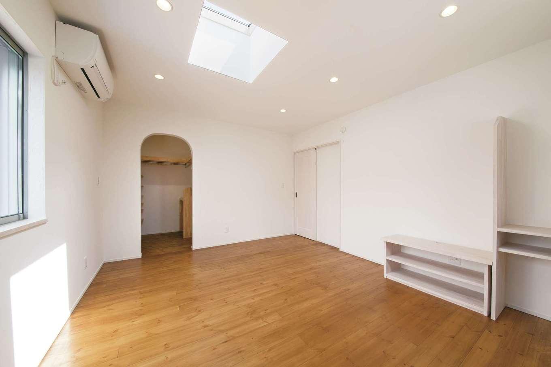 堀田建築【収納力、二世帯住宅、自然素材】Nさん夫妻の寝室は、天窓付きで明るい。アーチ型開口の奥にはウォークインクローゼットがある