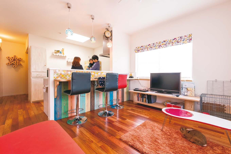 2階ワンフロアがNさん夫妻の居住空間。2階リビングは、花梨の無垢フローリングと、白い塗り壁のコントラストが目に心地いい。キッチンカウンター下の板は、奥さまが水性塗料でペイントしたもので、色の組み合わせにセンスが光る