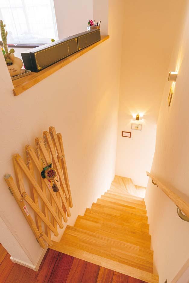 階段スペースは、木の踏み板と塗り壁、照明のグラデーションが美しい。採光を考えて壁の一部を抜き、視線と光が抜ける造りに