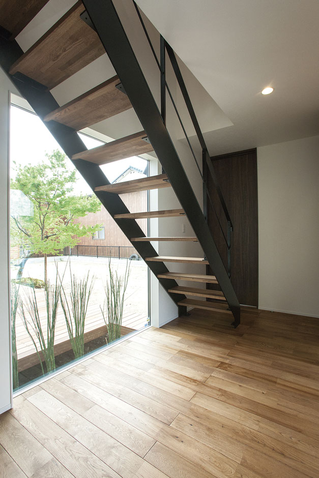 ARRCH アーチ【デザイン住宅、間取り、建築家】玄関ホールに明かりを届ける大きなピクチャーウインドウ。ウッドデッキにある坪庭やシンボルツリーが訪れる人の目を楽しませる