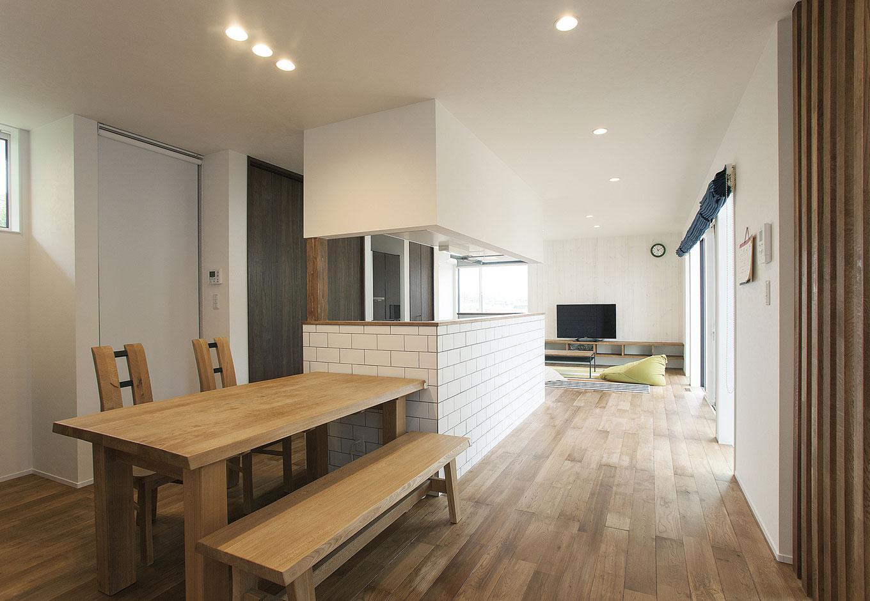 ARRCH アーチ【デザイン住宅、間取り、建築家】白いタイル貼りのキッチンを中心に、ダイニングとリビングが一直線につながるLDK。キッチンの立ち上がりを高くすることで手元や調理道具が見えず、すっきりとした印象に