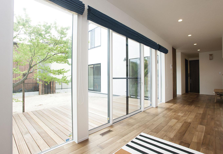 ARRCH アーチ【デザイン住宅、間取り、建築家】リビングの横にはゆったりとしたウッドデッキが広がる。たっぷりの光が差し込み、内と外がゆるやかにつながり、床面積以上の広がりを感じられる。大きなモミジの木が四季折々の景色を演出する