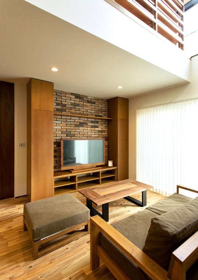 ARRCH アーチ【収納力、狭小住宅、建築家】テレビボードの背面にあしらったレンガ調の壁が、ナチュラルなLDKのアクセントに。左右には背の高い収納を用意して、掃除機といった普段使いする道具を収納