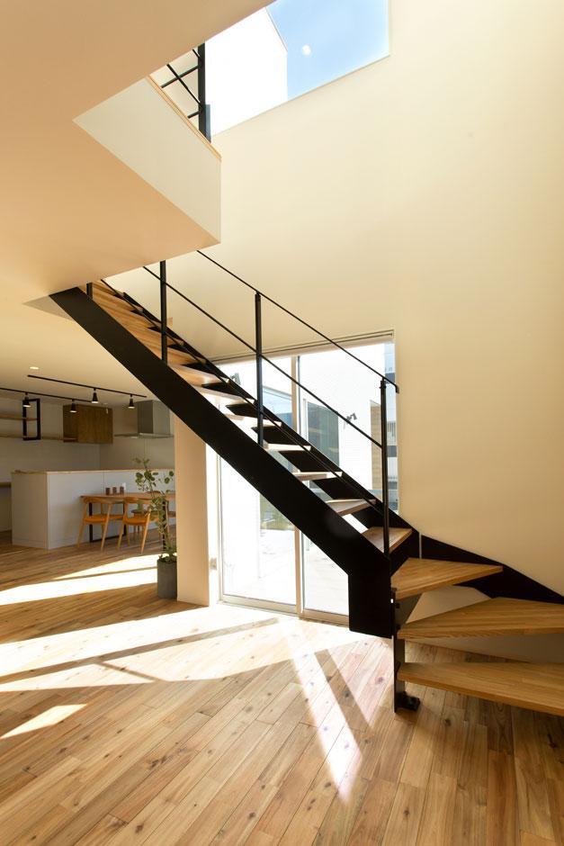 ARRCH アーチ【子育て、間取り、建築家】吹き抜けの窓から光が降り注ぐ純白の空間にアイアンの階段が映える。あえて南を向く窓の前に階段を置くことで、道路からの視線をカット。蹴込み板のないスケルトン階段だから、光や風が抜け、快適性は十分