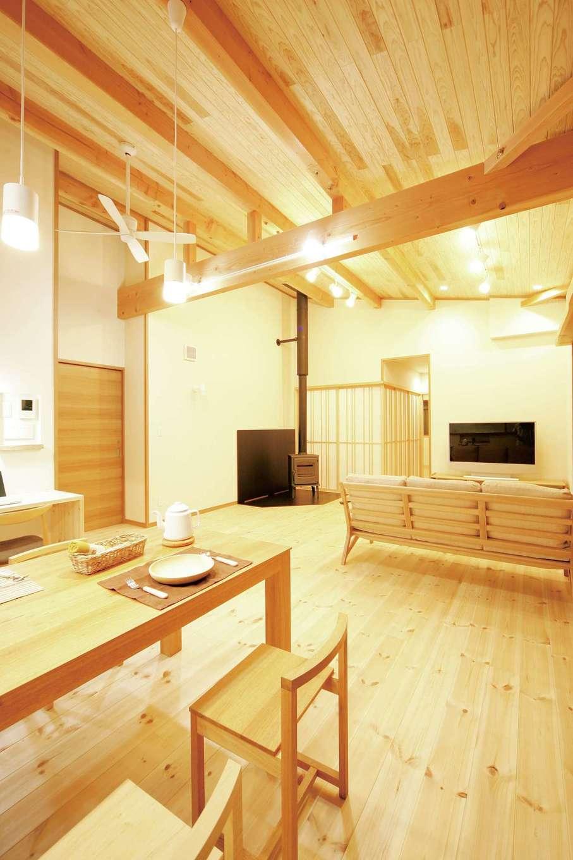 住まいるコーポレーション【デザイン住宅、自然素材、平屋】太い化粧梁と杉板張りの天井が美しい勾配天井のLDK。リビングの奥には薪ストーブがある