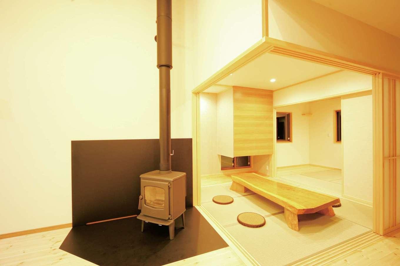 住まいるコーポレーション【デザイン住宅、自然素材、平屋】薪ストーブのコーナーと続き間の和室。採光や風通しを考えて収納の下に地窓を設置。子どもがお昼寝をするときに地窓を開けておくと、気持ちいいそよ風が入る。和室の奥には寝室があり、二部屋をつなげて利用できる