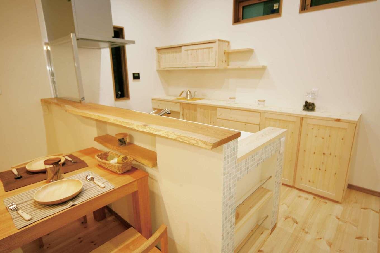 住まいるコーポレーション【デザイン住宅、自然素材、平屋】キッチンの収納棚は『住まいる』のオリジナル。収納の量や棚の高さ・位置はすべて奥さまの使い勝手に合わせて設計。対面キッチンの腰壁を少し高くしてあるので、キッチンの作業スペースや調理の手元を隠すことができる