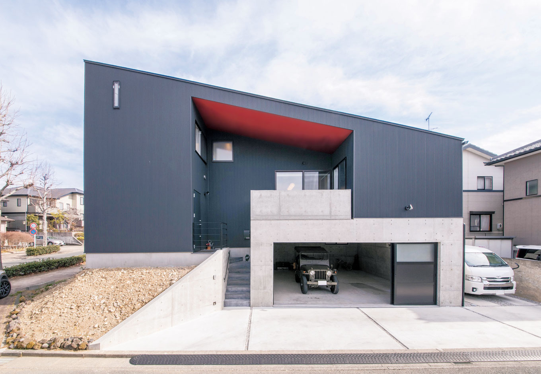 MABUCHI【趣味、スキップフロア、ガレージ】建築家の家らしいエッジの効いた外観フォルム。赤い軒天がポイントカラーになっている