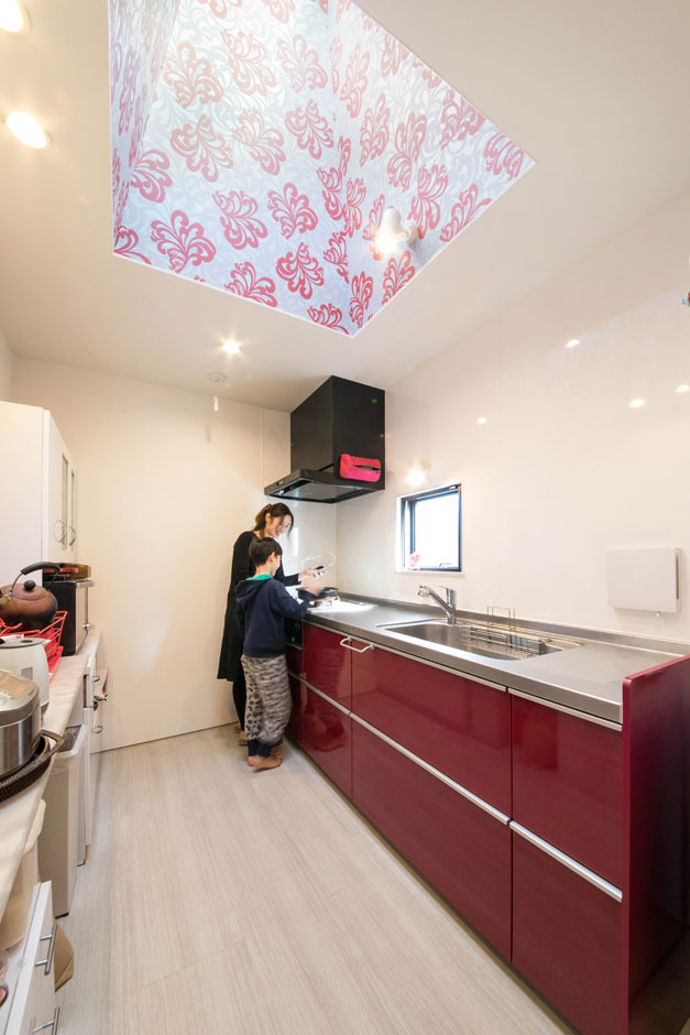MABUCHI【趣味、スキップフロア、ガレージ】個室型のキッチン。天窓の華やかなクロスは建築家が奥さまのイメージに合わせて選んだ
