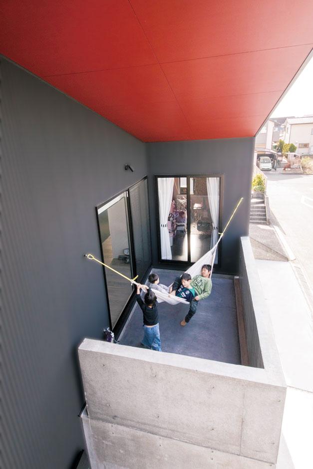 MABUCHI【趣味、スキップフロア、ガレージ】光と風を取り込むインナーテラスは、子どもたちの絶好の遊び場になっている。ハンモックを吊るしても、コンクリートの高い塀で目隠しされているので、プライバシーを確保しながら楽しめる。帽子のつばのような深い軒が夏の陽射しを遮り、冬は室内の奥まで光を届けてくれるパッシブデザインで光熱費も節約できる