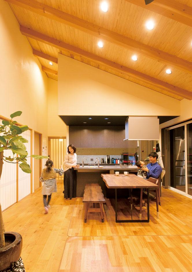 """ダイナミックな勾配天井のLDKは、平屋であることを忘れてしまうほどの開放感がある。無垢の木と漆喰が湿気を吸ったり吐いたりする""""呼吸する住まい""""は、家族にやさしく寄り添い、エアコンに頼り過ぎることなく、夏も冬も快適に過ごせる"""