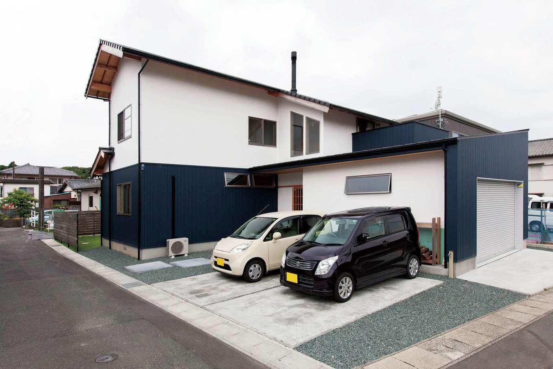 白と濃紺のコントラストが美しいシンプルモダンの外観。ガレージの壁に薪置き場も作られた