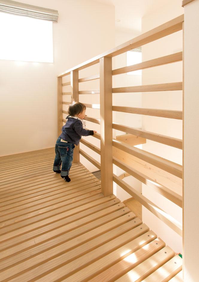 コバケンホーム(小林建設)【収納力、自然素材、間取り】吹抜けはLDKに開放感を与えると同時に、1階と2階に一体感をもたらし、どこにいても家族の気配を感じとれる空間を叶えた。キャットウォークは1階の明かり取りの役割と、子どもの好奇心や冒険心をくすぐる遊びのスペースとして活躍。子どもの指が床板の隙間に挟まらないように、板張りの間隔まで細かく配慮した