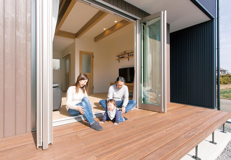 コバケンホーム(小林建設)【収納力、自然素材、間取り】全開口の窓を開け放つと、リビングとデッキが一体化して、屋外へと広がる開放感を楽しめる。デッキは屋根付きなので雨が降り込む心配もない
