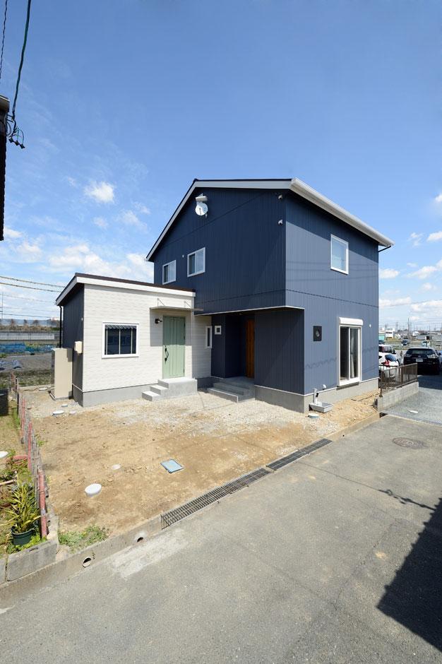 Yamaguchi Design 【デザイン住宅、自然素材、省エネ】ダークブルーと白のコントラストが美しい外観デザイン。外壁はガルバリウムのようにも見えるサイディングを採用し、コストダウンを実現