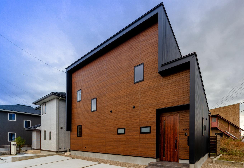 『nalabo』長坂篤建築研究所【デザイン住宅、収納力、建築家】ブラックのガルバリウム鋼板と木目調のサイディングが美しく調和した、建築家らしい外観デザイン。変形地を活かした建物の配置、片流れの屋根、木の軒天、窓の位置など、隅々まで緻密に計算されている