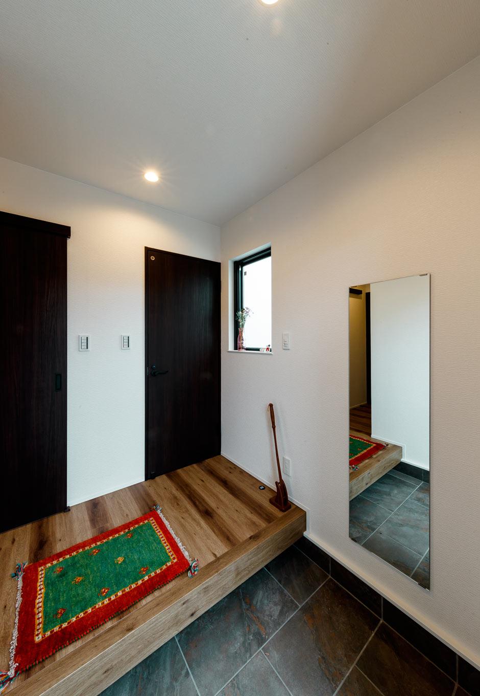 『nalabo』長坂篤建築研究所【デザイン住宅、収納力、建築家】木のぬくもりに満ちた玄関ホール。西側の小窓から十分な光を確保し、暗くなりがちな空間に明るさをもたらす。大きな姿見は靴までチェックできると同時に、空間を広く見せる効果もある