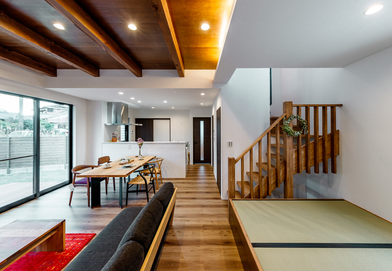 『nalabo』長坂篤建築研究所【デザイン住宅、収納力、建築家】床と天井に無垢板を使ったLDK。小さな子どもたちを見守りながら料理できる位置にキッチンを配置した。リビングの天井を上げ、梁を見せることでワンフロアの空間にメリハリをつけた