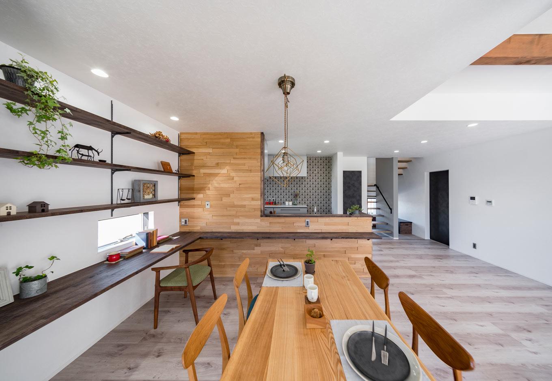 『nalabo』長坂篤建築研究所【子育て、建築家、スキップフロア】木のデザイン壁がおしゃれなキッチン。L字型のカウンターを造作し、PCコーナーに。飾り棚も造作し、雑貨やグリーンなど、見せる収納に