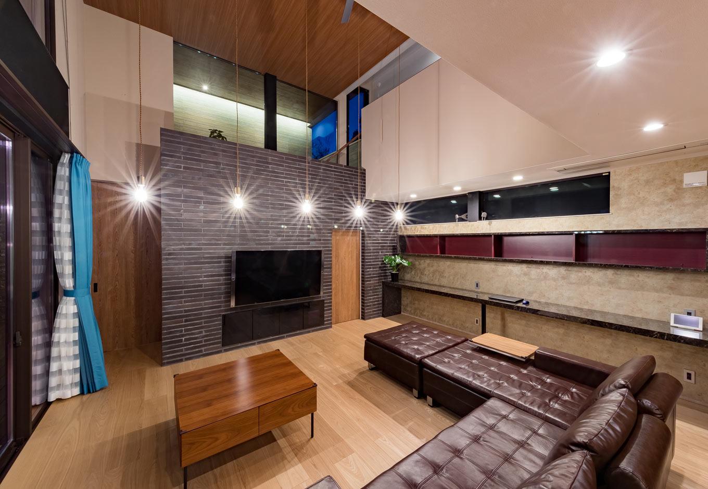 『nalabo』長坂篤建築研究所【デザイン住宅、子育て、建築家】ダイニング、キッチンとゆるやかにゾーン分けされたラグジュアリーなリビング。窓の位置と大きさ、間接照明の当て方も参考になる。タイル貼りのテレビステーションの裏から階段を上がればインナーテラスへとつながる
