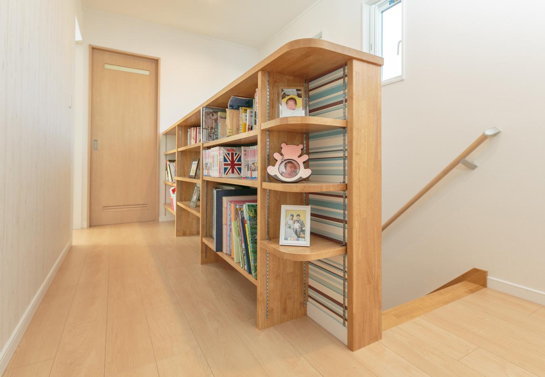 アイジーホーム 【二世帯住宅、省エネ、ペット】家族みんなで使うことができるホールの腰壁全面の本棚。本のみならず思い出の写真も飾る。子どもの絵本も手が取りやすい高さに