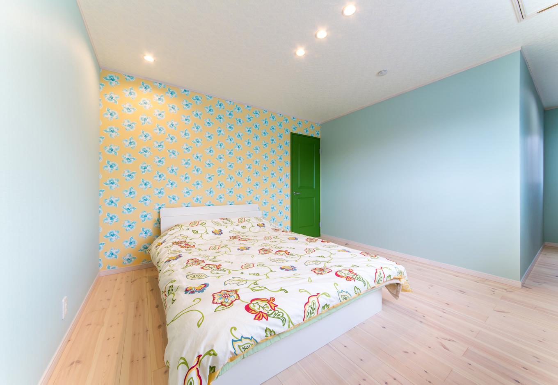 ビビットなグリーンのカラードアの寝室。天井には屋根裏収納
