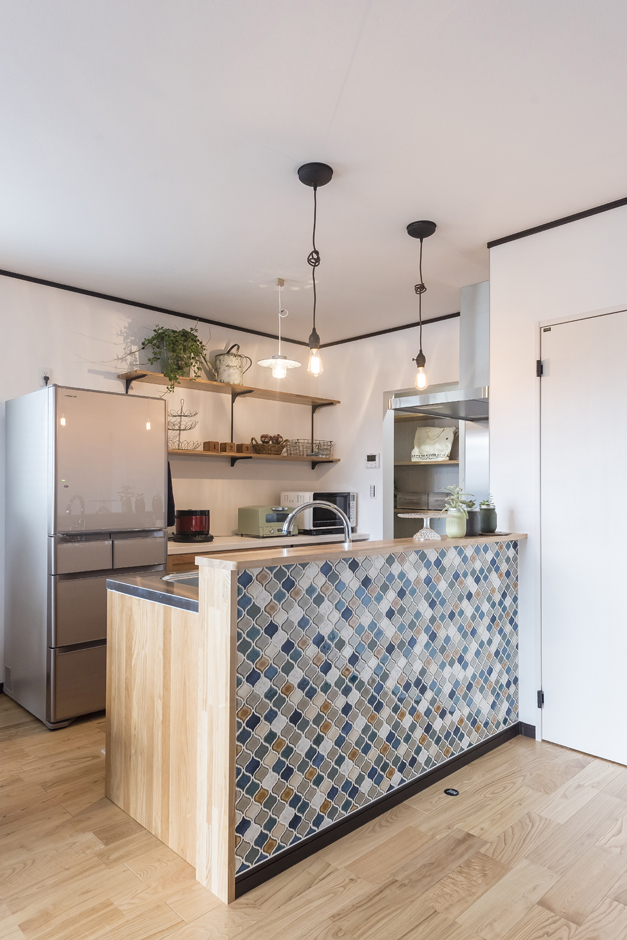 アイジーホーム 【デザイン住宅、収納力、インテリア】キッチンの壁にはランタン調のモザイクタイルを。明るめの配色で主張しすぎないのもポイント。収納は見えない部分にたっぷり設け、背面のオープンシェルフは飾り棚として好きな雑貨を飾っている