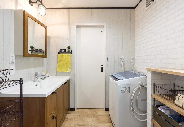 アイジーホーム 【デザイン住宅、収納力、インテリア】広めの洗面脱衣所には、収納ラック用のスペースを設けた。木製の洗面台とレンガ調のクロス、マリンテイストの照明でナチュラルな空間に。大きめのシンクが使いやすい