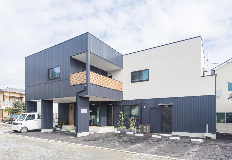 アイジーホーム 【デザイン住宅、収納力、インテリア】ガルバリウム鋼板と塗り壁の異素材の組み合わせがモダンな印象の外観。バルコニーの木調の壁もアクセントに。事務所の入り口の脇に住宅用の玄関を設け、家族の出入りも気兼ねなくできる