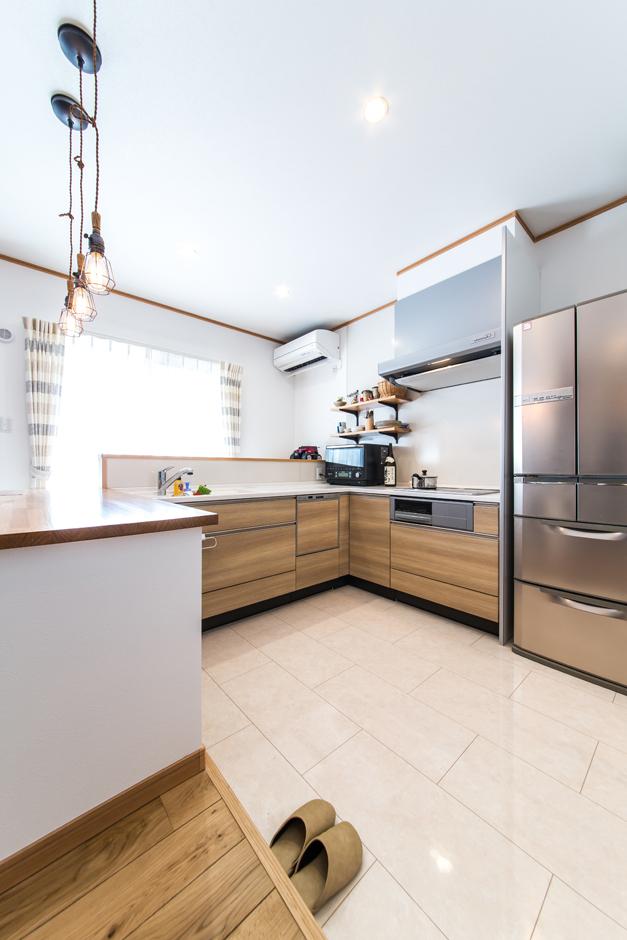 あえて段差をつけたキッチンはLDKとの空間を隔て、リビングで寛ぐ家族と一緒の空間にいながら奥さまだけの空間としての変化を。憧れのL字型のキッチンや見せる収納を現実に。よく使うお皿や雑貨を置いて理想の暮らしのインテリアを無理なく楽しみはじめている