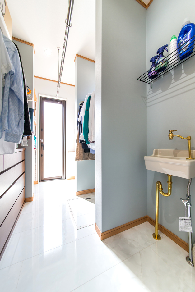 キッチン後ろのランドリールーム。洗濯機の横にはお子様の上履き洗い用のボウル。室内干し、アイロンがけ、洗濯物を畳んでしまう、よく着る衣服をハンガーにかけておく。一度に家事を終えることができるスペースは子育てママの女性目線ならではのアイデア