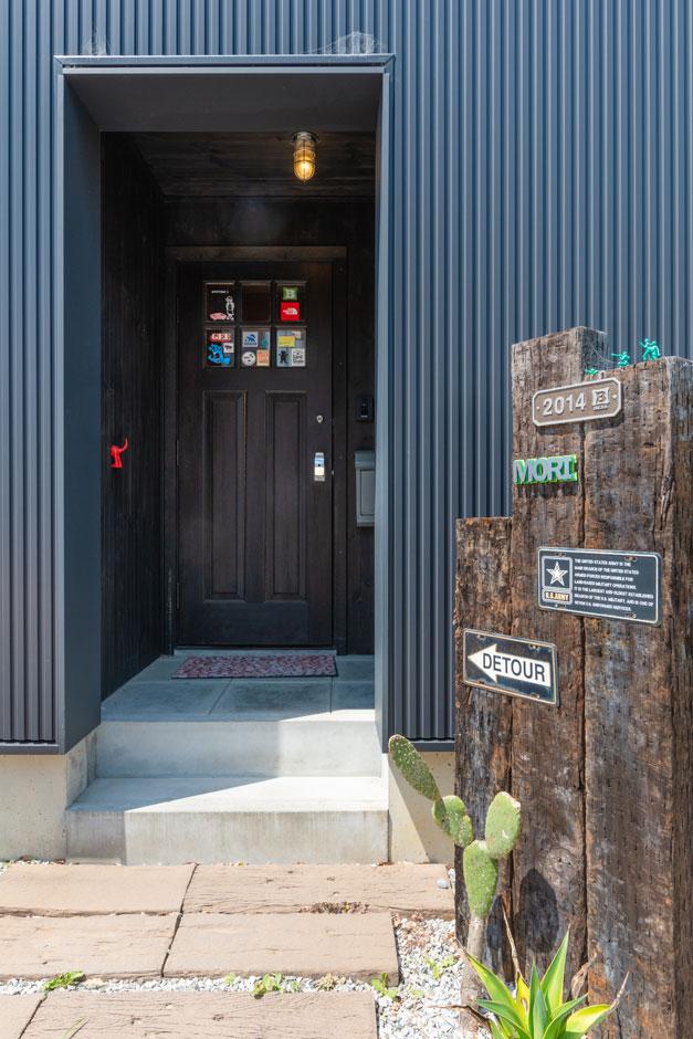 BESS浜松【子育て、趣味、自然素材】ガルバリウムの壁にぽっかり空いた穴がこの家の玄関。ステッカーを貼った玄関扉や、エントランスのサボテンが個性的でおしゃれ