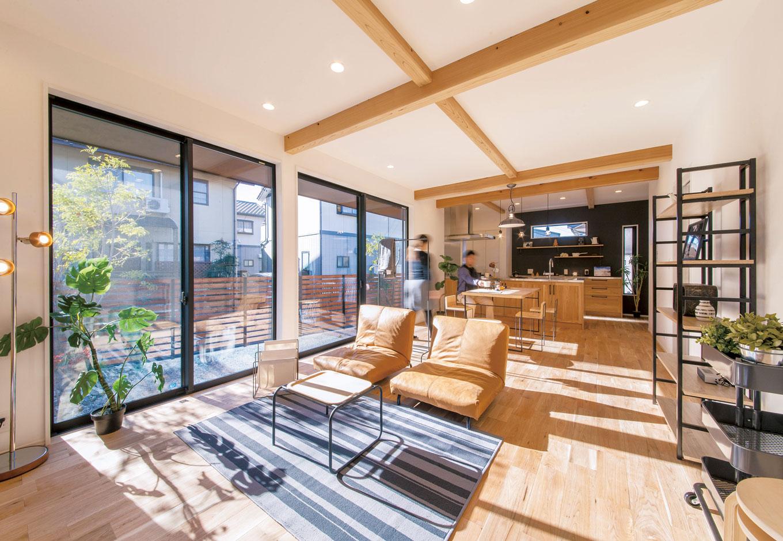 住たくeco工房【1000万円台、デザイン住宅、自然素材】クルミ無垢材のフローリングが美しい22畳のLDK。照明や家具など奥さまのコーデセンスが光る。梁は天竜材をラフな仕上げで。窓は通常の1.5倍幅、高さ2250cm。この大開口部も、樹脂サッシLow-Eペアガラスだから断熱も十分