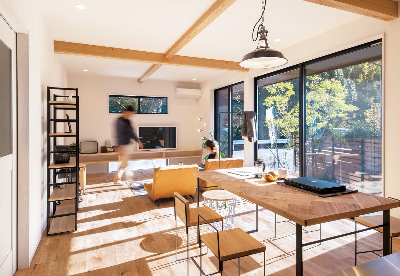 住たくeco工房【1000万円台、デザイン住宅、自然素材】TVボードの上部と下部にも窓を配し、外の緑を借景に視線の広がりをつくる。テーブルはオーダーメイド。床材に合わせクルミ材をヘリンボーン張りでおしゃれに。オリジナル家具がオーダーできるのも『住たくeco工房』の魅力