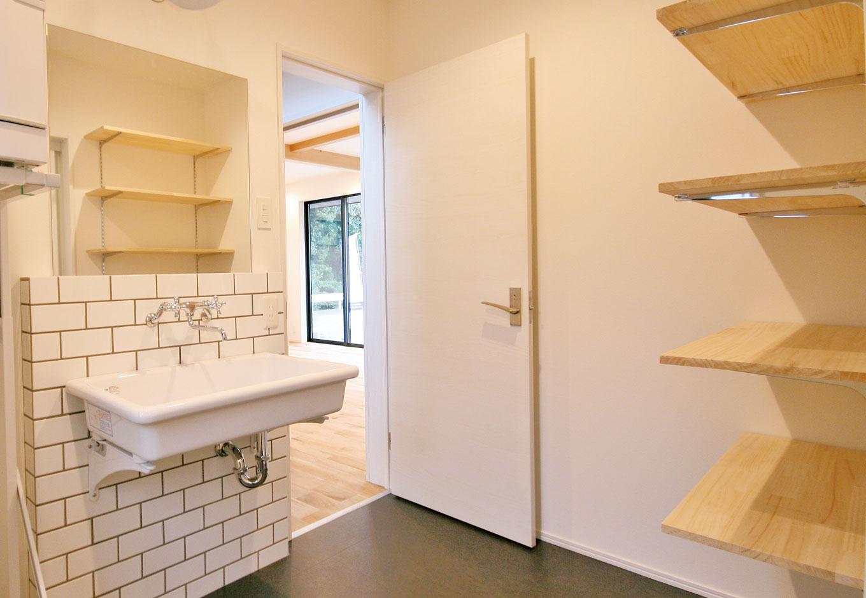 住たくeco工房【1000万円台、デザイン住宅、自然素材】白いタイルと四角く白い陶器のシンクでコーディネートした洗面所は、まるで理科室のよう。このTOTO製シンクは「実験用シンク」とも呼ばれ、インダストリアルデザインともマッチする密かな人気アイテム