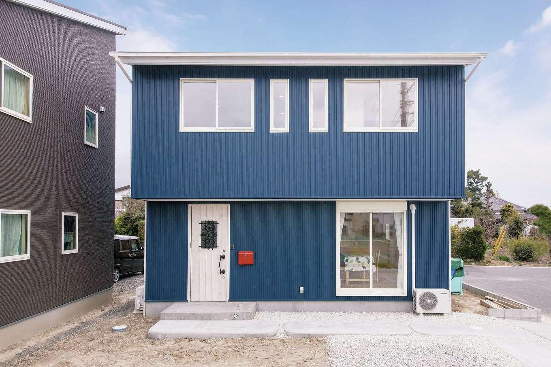 アキケンチク【デザイン住宅、収納力、趣味】紺色のガルバリウム鋼板が覆うスクエアな外観に、アイアンをあしらった白い玄関扉と赤のポストが映える