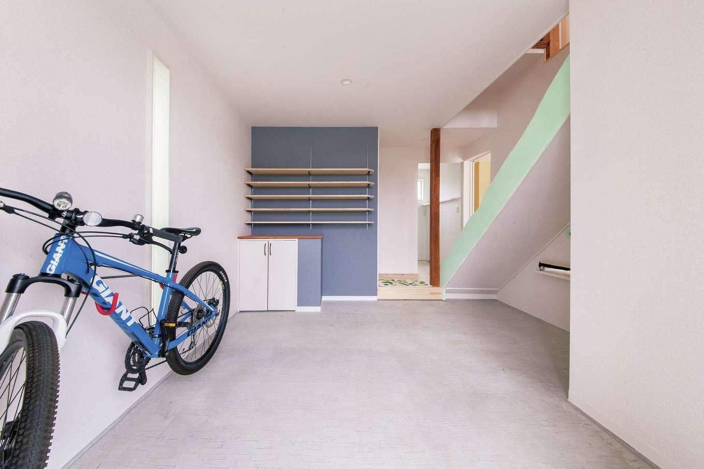 アキケンチク【デザイン住宅、収納力、趣味】扉を開けるとゆったりとした玄関土間がお出迎え。ご主人が自転車のメンテナンスや筋トレをするほか、雨の日にはお子さんが縄跳びを楽しむなど、マルチに活躍