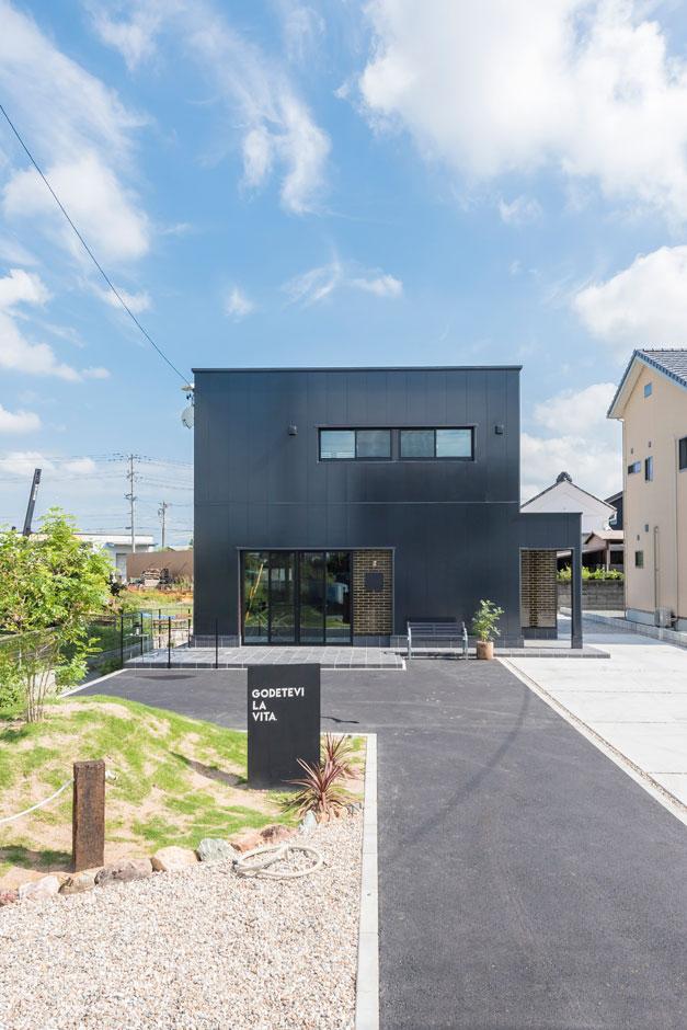 R+house 浜松中央(西遠建設)【趣味、建築家、インテリア】家の前にはイタリア語で「人生を楽しむ」と書かれたデザインが。人が集まれるように駐車スペースもたっぷり確保