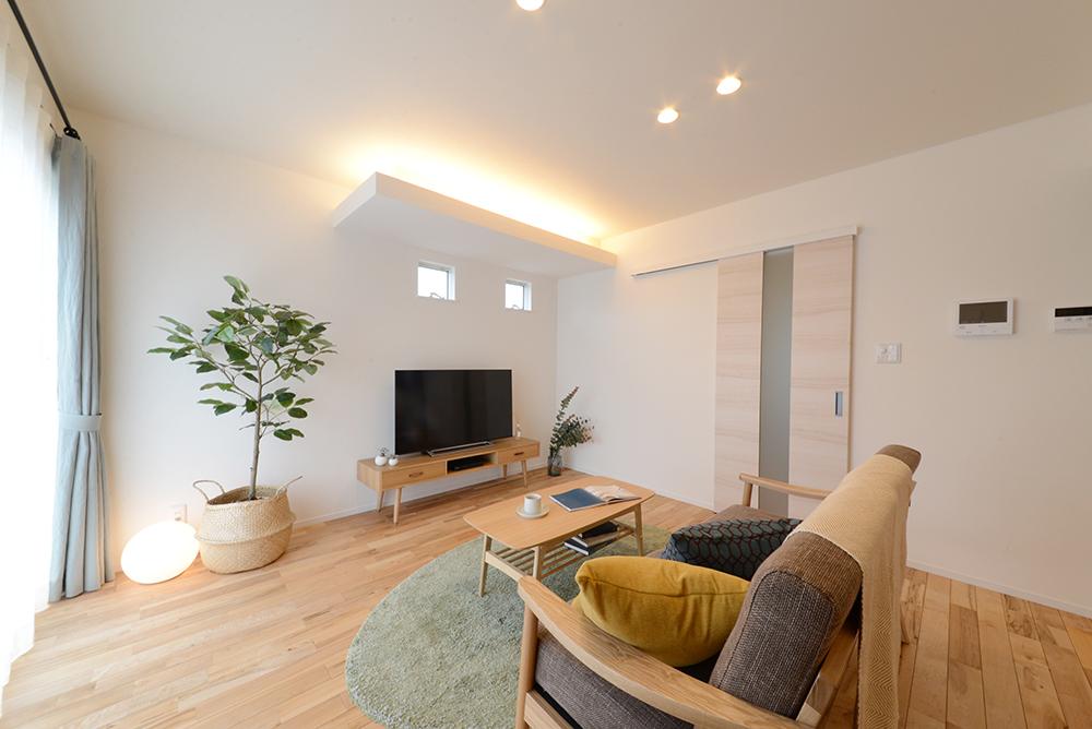静鉄ホームズ【コアハウス】【焼津市三ケ名877-3・モデルハウス】コアハウスは塗り壁&無垢床の自然素材が標準仕様。リビングの一角には下がり天井と間接照明を採用し、優しい灯りで塗り壁を照らしている。