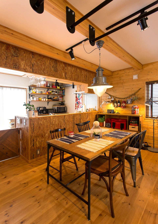 BESS浜松【子育て、趣味、インテリア】キッチン前面を覆うのは、頑丈で味わいのあるOSB合板。板表面の、性能基準合格を記すスタンプをあえて見せることで、ガレージのような風合いを出した。ダイニングチェアはすべてデザインが違うが、それさえもお洒落に映える。天井には鉄棒を設置する遊び心も