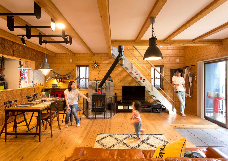 BESS浜松【子育て、趣味、インテリア】通常よりも土間を減らし、吹き抜けを小さくして2階居室を増やしたため、居住空間が広くなった。床と壁はすべてパイン無垢材で、薪ストーブや家具の黒いアイアンが空間を引き締める。壁に吊るされたキャンプ用品や掃除道具さえ、インテリアの一部に