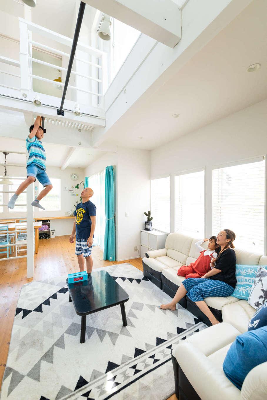 Select工房【デザイン住宅、趣味、インテリア】キッチン、ダイニング、リビングをL字型に繋いだLDK。「家中を明るくしたい」という奥さまのオーダーにより、天井高を上げて窓を大きくとり、部屋中に光を取り込んでいる。「室内に遊び場が欲しい」というご主人の要望から、リビング上部に鉄棒を設置。子どもたちもお気に入りだ