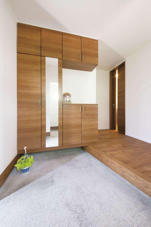 原田工務店【デザイン住宅、自然素材、平屋】玄関の土間は、ポーチと同様に趣のある洗い出し仕上げにして、落ち着きを演出。天井まで届く収納ですっきりとした空間を保てる