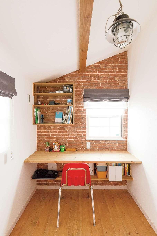 """富士ホームズデザイン【1000万円台】ご主人の書斎はデザイン壁と照明で""""隠れ家感""""をプラス。背後には一面の本棚が備えられている"""