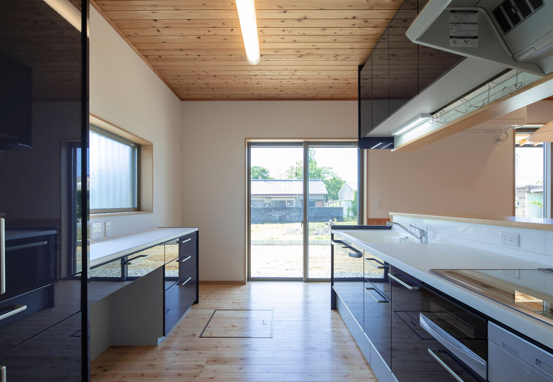 友和建設【収納力、自然素材、間取り】キッチンはシックなカラーで引き締めて。複数人でも作業がしやすいゆとりのある設計。対面式で子どもにも目が行き届く