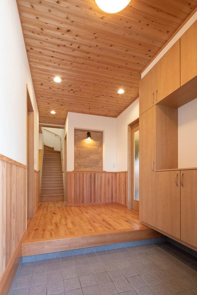 友和建設【収納力、自然素材、間取り】玄関ホールから廊下も、天井・床ともすべて無垢材を使用。白壁と天然木のコントラストが美しい。正面のニッチを利用した飾り棚がアクセント