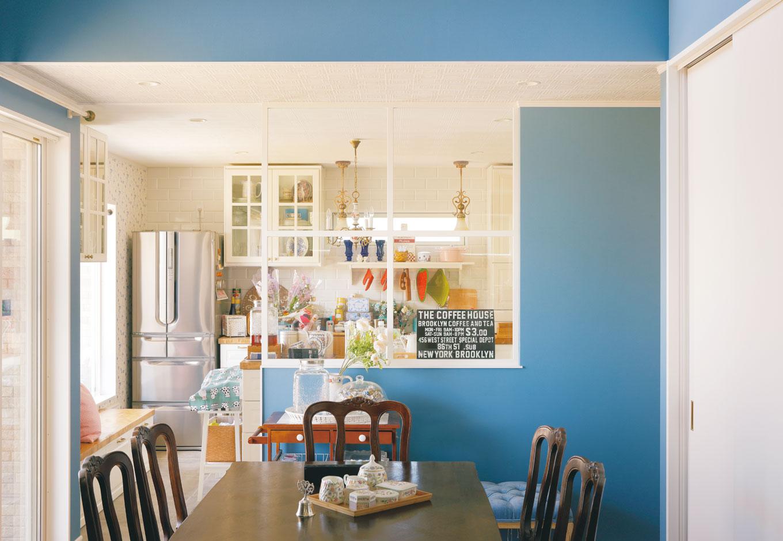 幹工務店【デザイン住宅、輸入住宅、インテリア】キッチンは独立型で、白を基調にデザイン。窓際のベンチの横には猫の出入口も確保した。ダイニングとの間にはガラス入り格子建具を設け、抜け感を強調