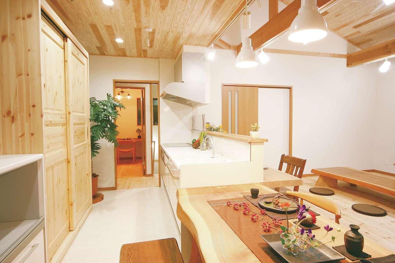 住まいるコーポレーション【和風、二世帯住宅、自然素材】対面キッチンはダイニングテーブルと並べて配置。キッチンの手前にはタモの無垢材のカウンターがある。背面には、高さや幅、奥行きまで奥さまの使い勝手にぴったり合わせたオリジナルの造作食器棚を設置