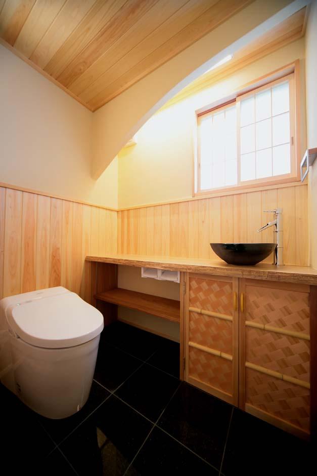 エコフィールド【和風、二世帯住宅、自然素材】檜のカウンターに焼き物の洗面ボウル、竹を組み合わせた斜め格子模様の収納扉など、トイレにも和の趣があふれる