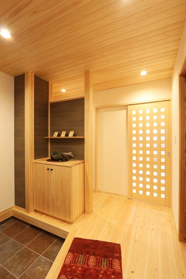 天井に使用した檜羽目板が光を柔らかく広げ、玄関を優しく穏やかな雰囲気に